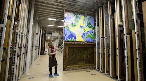 "Press and communications officer Veronique Van Passel pulls out a sliding panel of paintings at the interior warehouse of the Antwerp Royal Museum of Fine Arts in Antwerp, Belgium on Thursday, April 4, 2013. Just as the famous Amsterdam Rijksmuseum in neighbouring Netherlands has returned ""The Night Watch"" of its most famous painter, Rembrandt van Rijn, back in the main building after a ten-year renovation, Antwerp is hiding five oversized Rubens paintings in a special depot to protect them against the rough and tumble of four more years of works. (AP Photo/Virginia Mayo)"