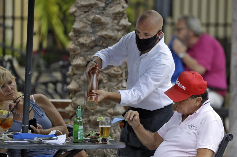 A food server wearing a protective face mask waits on customers at the Parkshore Grill restaurant Monday, May 4, 2020, in St. Petersburg, Fla. Several restaurants are reopening with a 25% capacity as part of Florida Gov. Ron DeSantis' plan to stop the spread of the coronavirus. (AP Photo/Chris O'Meara)
