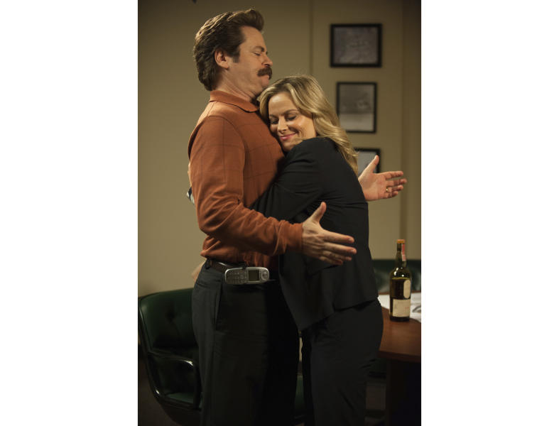 """In this image released by NBC, Nick Offerman, left, and Amy Poehler appear in a scene from """"Parks and Recreation."""" The cast will reunite for """"A Parks and Recreation Special"""" on Thursday, April 30 at 8:30 p.m. ET. (Colleen Hayes/NBC via AP)"""