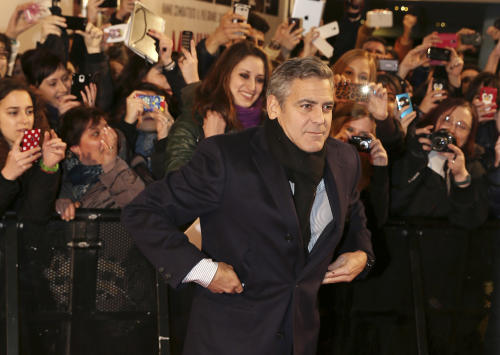 """American actor George Clooney poses for photographers on the red carpet for the screening of the movie """"Monuments Men """", in Pioltello, near Milan, Italy, Monday, Feb. 10, 2014. (AP Photo/Antonio Calanni)"""