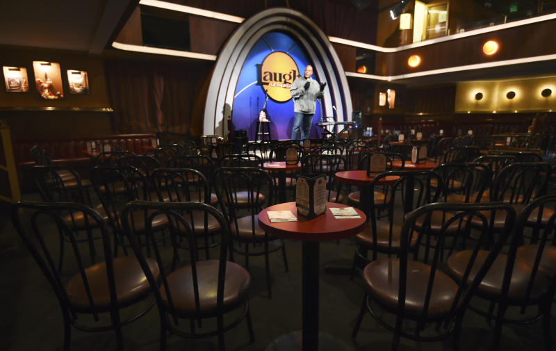 """In this April 20, 2020, photo, empty chairs face comedian Alonzo Bodden as he performs during a """"Laughter is Healing"""" stand-up comedy livestream event at the Laugh Factory in Los Angeles. With comedy clubs closed and concert tours put on hold, comics like Craig Robinson, Tiffany Haddish, Will C  and others are keeping the jokes flowing on webcasts and Zoom calls even without the promise of a payday, because they say the laughs are needed now more than ever. (AP Photo/Chris Pizzello)"""