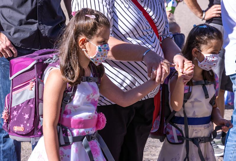01 August 2020, Mecklenburg-Western Pomerania, Schwerin: Nele (l) and Lena (r) go with their mother Nicole Baschke wearing face masks to the school enrolment ceremony at the Lankow primary school. In Mecklenburg-Vorpommern's elementary schools, around 13,900 first-graders are enrolled, taking into account the corona protection measures. On 03.08.2020, regular school operations will begin again in the north-east. Photo: Jens Büttner/dpa-Zentralbild/dpa (Photo by Jens Büttner/picture alliance via Getty Images)