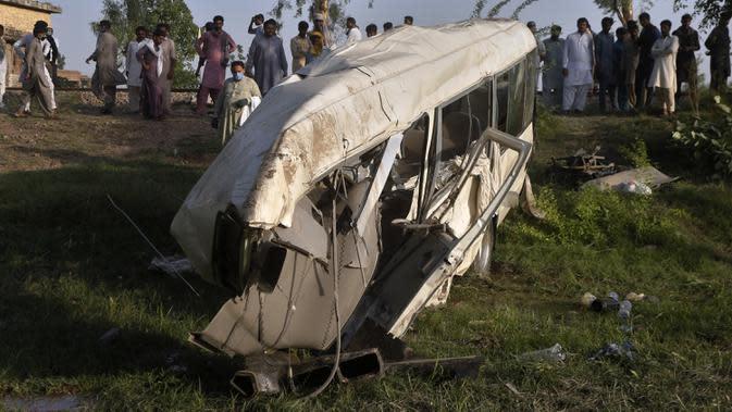 Warga berkumpul dekat puing-puing bus yang tertabrak kereta api di Farooq Abad, Distrik Sheikhupura, Pakistan, Jumat (3/7/2020). Bus yang membawa peziarah Sikh tersebut melewati perlintasan tak berawak ketika ditabrak oleh kereta yang melaju dekat kota kecil Farooqabad. (AP Photo/K.M. Chaudary)
