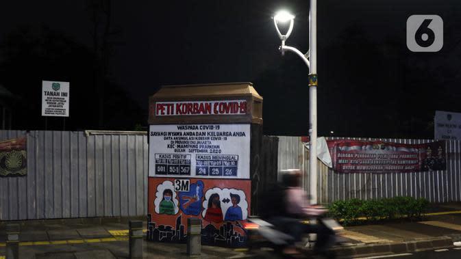 Warga melintas di dekat instalasi peringatan bahaya COVID-19 di kawasan Kemang, Jakarta, Selasa (15/9/2020). Guna mengurangi pola penyebaran COVID-19, Pemda DKI Jakarta kembali menerapkan PSBB dengan membatasi aktivitas warga, perdagangan maupun perkantoran. (Liputan6.com/Helmi Fithriansyah)