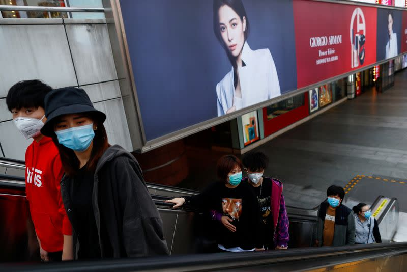 People wearing protective masks walk in a shopping district in Beijing