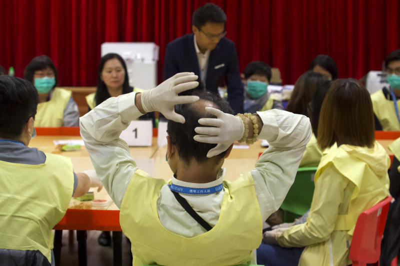 An election worker reacts after sorting through ballots at a polling station in Hong Kong, early Monday, Nov. 25, 2019. Voters in Hong Kong turned out in droves on Sunday in district council elections seen as a barometer of public support for pro-democracy protests that have rocked the semi-autonomous Chinese territory for more than five months. (AP Photo/Ng Han Guan)