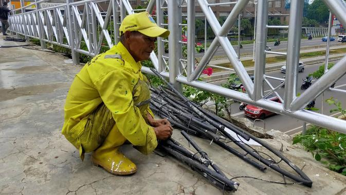 Petugas memperbaiki saluran air di JPO tanpa atap di Jalan Sudirman, Jakarta Rabu (6/11/2019). (Liputan6.com/ Rizki Putra Aslendra)