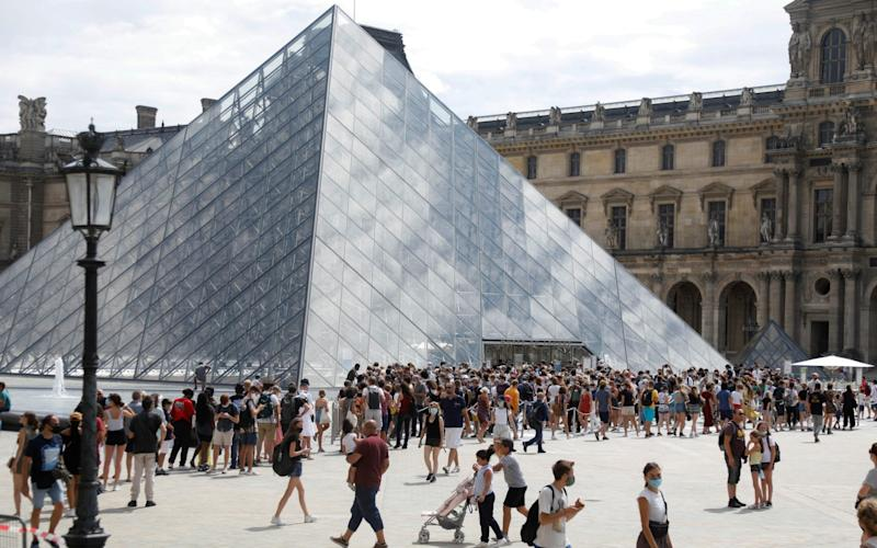 Visitors wearing protective face masks queue to enter the Louvre Pyramid in Paris - Charles Platiau/Reuters