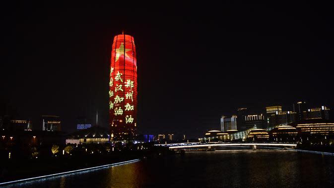 Sebuah bangunan memancarkan sejumlah slogan sebagai penghormatan bagi orang-orang yang berjuang melawan virus corona COVID-19 di Zhengzhou, Provinsi Henan, China, Sabtu (21/3/2020). Wabah COVID-19 di China saat ini sudah mulai mereda. (Xinhua/Zhu Xiang)