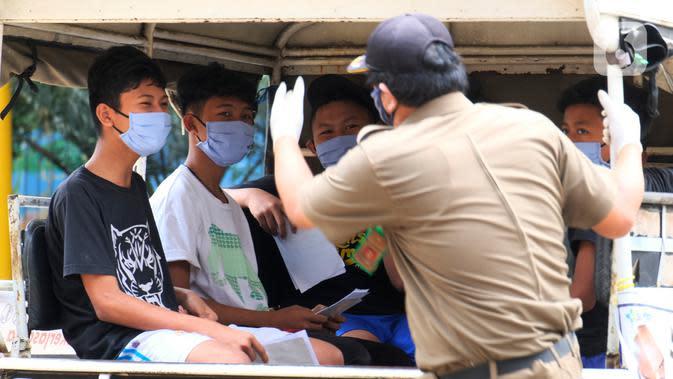 Warga pelanggar PSBB diangkut mobil Satpol PP di Tangerang, Kamis (14/5/2020). Pemkot Tangerang melakukan tindakan bagi pelanggar PSBB seperti tidak menggunakan masker dengan membawa mereka ke kantor Kecamatan Karawaci Baru untuk dilakukan pemeriksaan Rapid Test COVID-19. (Liputan6.com/Angga Yuniar)