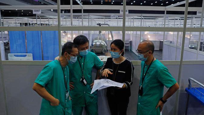 Pekerja medis membuat persiapan di rumah sakit lapangan sementara yang didirikan di Asia World Expo di Hong Kong, Sabtu (1/8/2020). Pusat pameran di dekat Bandara Internasional Hong Kong itu diubah menjadi fasilitas untuk menampung pasien COVID-19 dengan gejala ringan. (AP Photo/Kin Cheung)