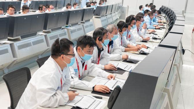 Para personel teknis bekerja di Pusat Kendali Antariksa Beijing (Beijing Aerospace Control Center/BACC) di Beijing, ibu kota China (9/10/2020). Wahana penjelajah tersebut menyelesaikan manuver orbital pada pukul 23.00 setelah mesin utamanya bekerja selama lebih dari 480 detik. (Xinhua/Cai Yang)