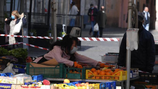 Pedagang buah-buahan mengenakan masker saat berjualan di sebuah pasar di Roma, Italia, 6 April 2020. Menurut Departemen Perlindungan Sipil Italia pada 6 April 2020, jumlah kasus virus corona COVID-19 di negara tersebut menjadi 132.547 dengan angka kematian mencapai 16.523. (Xinhua/Augusto Casasoli)