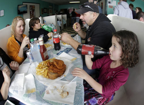In this Friday, March 23, 2013 photo, Madison Lehman, 5, right, takes a drink after tasting her first piece of hot chicken at Prince's Hot Chicken Shack in Nashville, Tenn. Hot chicken -- fried chicken with varied amounts of seasoning that make the heat level run from mild to extra hot -- is a signature dish of Nashville. Also shown are Cherie Salazar, left, Joey Lehman, 11, and Manny Salazar. (AP Photo/Mark Humphrey)