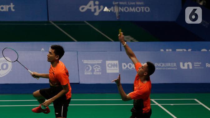 Ganda putra Indonesia, Fajar Alfian/Muhammad Rian Ardianto mengembalikan kok ke arah pasangan Malaysia, Aarron Chia/Soh Wooi Yik pada final bulutangkis beregu putra SEA Games 2019 di Multinlupa Sport Center, Rabu (4/12/2019). Fajar / Rian kalah 17-21 dan 13-21. (Bola.com/M Iqbal Ichsan)