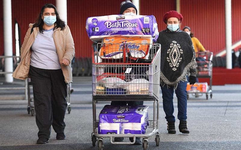 People push their trolleys outside a Costco outlet in Melbourne on Sunday - WILLIAM WEST/AFP