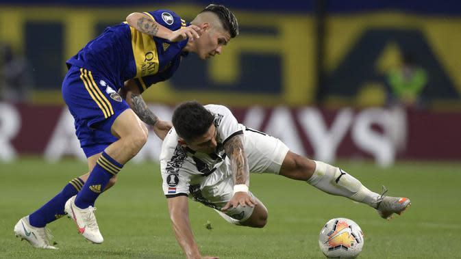Gelandang Boca Juniors, Jorman Campuzano, berebut bola dengan gelandang Libertad, Matias Espinoza, pada laga grup H Copa Libertadores di Estadio La Bombonera, Rabu (30/9/2020) dini hari WIB. Boca Juniors bermain imbang 0-0 atas Libertad. (Juan Mabromata/Pool via AP)