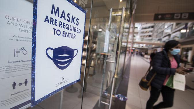 Seorang wanita yang mengenakan masker berjalan melewati toko dengan pemberitahuan kewajiban untuk memakai masker di CF Toronto Eaton Center, Toronto, Kanada, 6 Oktober 2020. Jumlah kasus harian COVID-19 di Kanada terus bertambah. (Xinhua/Zou Zheng)