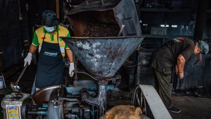Pekerja menuangkan kopi ke dalam dalam kaleng untuk dijual di Pabrik Kopi Antong, Taiping, Perak, Malaysia, 29 September 2020. Pabrik Kopi Antong menggunakan mesin antik dan metode pemanggangan tradisional untuk menghasilkan bubuk sarat kafein yang terkenal selama 87 tahun. (Mohd RASFAN/AFP)