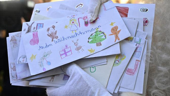 Seorang pria sebagai Father Christmas memegang surat daftar harapan anak-anak saat pembukaan kantor pos Sinterklas di Himmelpfort, Jerman, Kamis (14/11/2019). Setiap tahunnya ada sekitar ratusan ribu surat yang masuk dari 64 negara yang harus dijawab Santa. (Tobias SCHWARZ / AFP)
