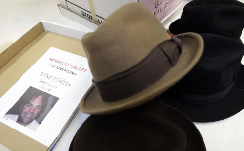 """A flyer advertising a costume fitting for Mike Piazza, former MLB baseball player, is shown with an assortment of hats, while Piazza is fitted for his costume for his role in """"Slaughter on Tenth Avenue"""" at the Miami City Ballet, Tuesday, April 16, 2013, in Miami Beach, Fla. Piazza plays a gangster in the ballet. (AP Photo/Lynne Sladky)"""
