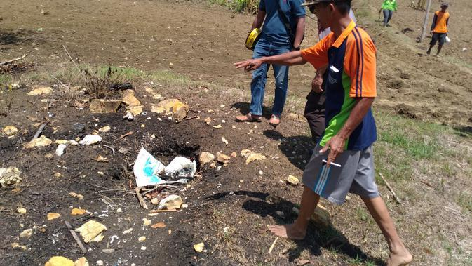 Piyono saat menunjukkan titik semburan kecil yang dulunya muncul api kecil seperti api abadi di Mrapen, Grobogan. Saat ini, sudah padam karena ditutup bebatuan oleh warga (Liputan6.com/Ahmad adirin)