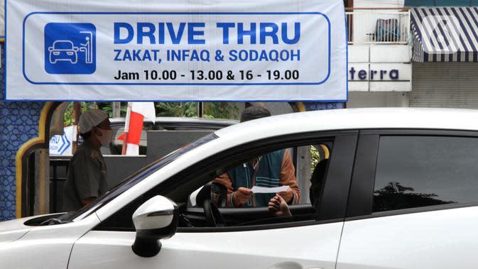 ZAKAT DRIVE THRU: Petugas melayani warga yang membayar zakat fitrah melalui sistem drive thru di Masjid Nurul Hidayah, Tanah Kusir, Jakarta, Selasa (19/5/2020). Layanan zakat drive thru selama pandemi COVID-19 ini diberlakukan dengan protokol kesehatan dan keselamatan. (Liputan6.com/ Johan Tallo)