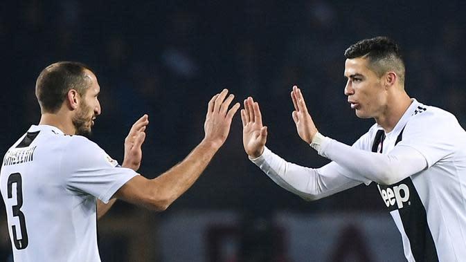 Pemain Juventus, Cristiano Ronaldo (kanan) mendekati Giorgio Chiellini usai mencetak gol ke gawang Torino dalam Serie A Italia di Stadion Olimpiade, Turin, Italia, Sabtu (15/12). Gol Ronaldo menjadi gol ke-5.000 Juventus di Serie A. (Marco BERTORELLO/AFP)