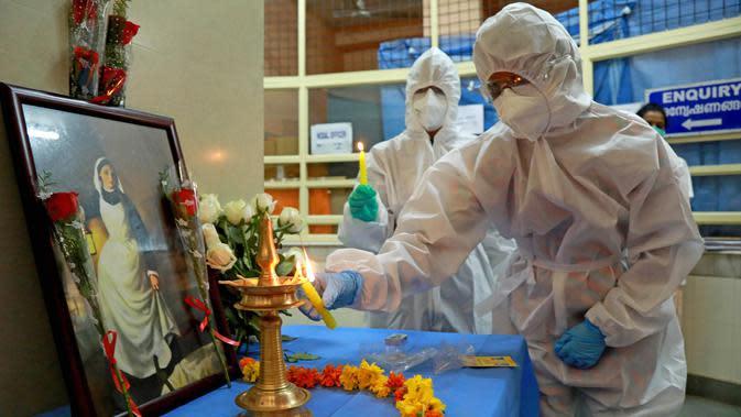 Perawat menyalakan lampu minyak di depan gambar Florence Nightingale saat peringatan Hari Perawat Internasional di Ernakulam Medical College, Kochi, India, Selasa (12/5/2020). Pada tahun ini, Hari Perawat Internasional bertema Nursing the World to Health. (Arun CHANDRABOSE/AFP)