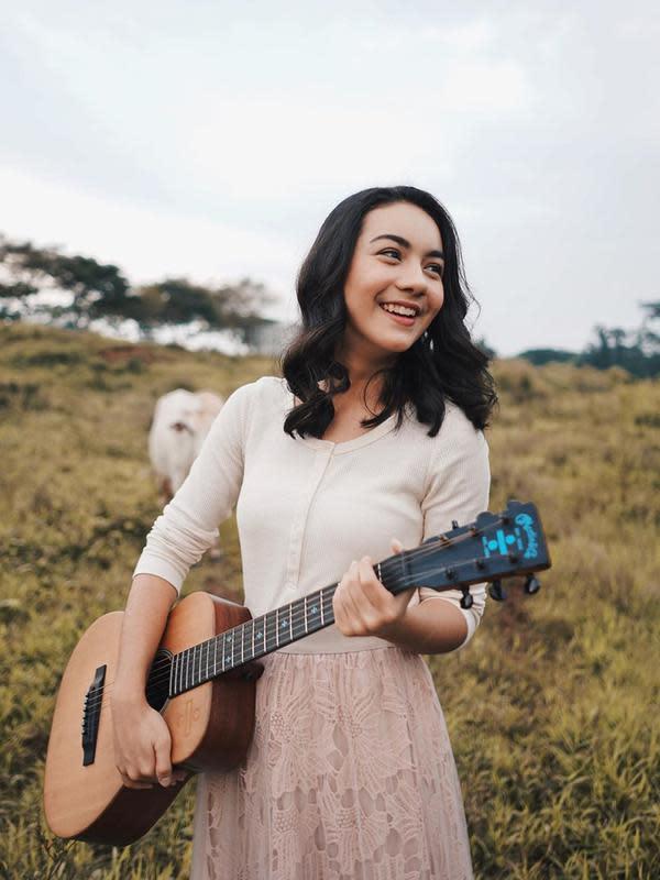 Seperti ketika ia sedang menikmati pemandangan ladang rumput dengan sapi-sapi. Ersya tampak cantik dengan atasan putih dan rok panjang berwarna merah muda serta memegang gitar. (Liputan6.com/IG/@ersyaurel)
