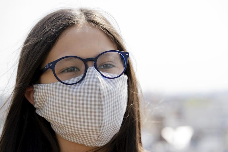 Portrait of teenage girl wearing homemade face mask to protect her health from coronavirus