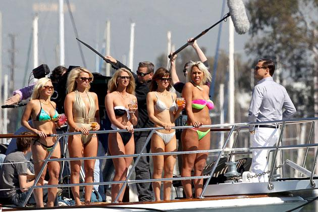 Rough life: After skipping the Oscars, Leo DiCaprio is spotted filming on a yacht with bikini-clad women
