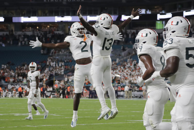 Miami running back DeeJay Dallas (13) celebrates with wide receiver K.J. Osborn (2) after scoring a touchdown during the first half of an NCAA college football game against Virginia, Friday, Oct. 11, 2019, in Miami Gardens, Fla. (AP Photo/Lynne Sladky)