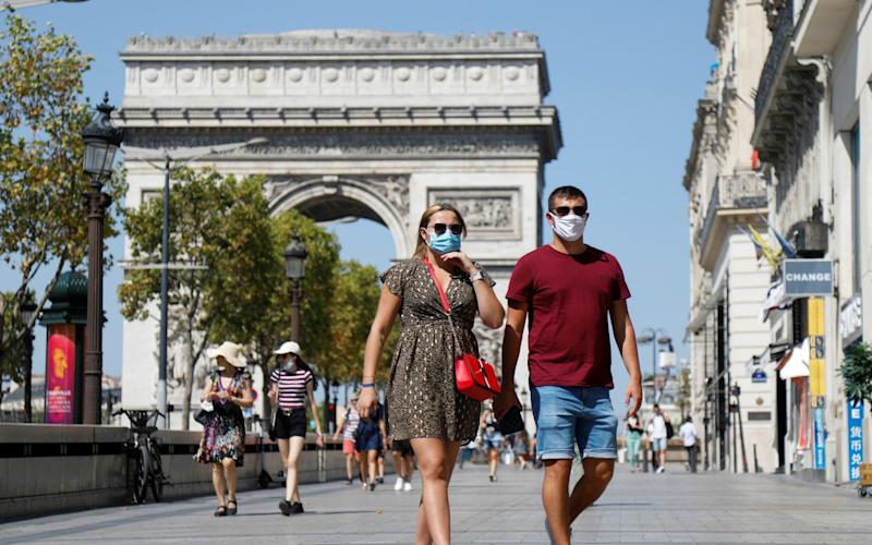 Pedestrians obey the rules along the Champs-Elysees near the Arc de Triomphe, as France reinforces the use of masks - REUTERS/Charles Platiau
