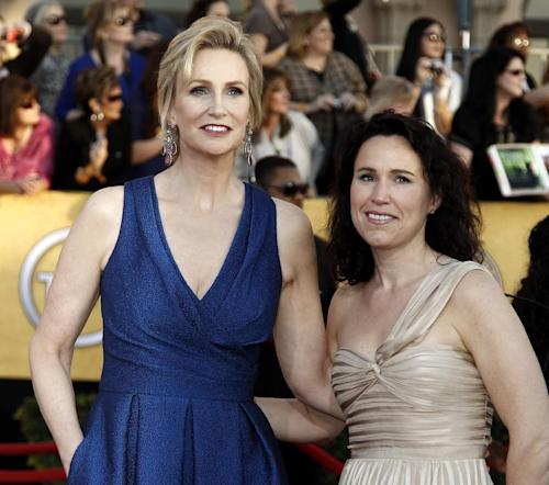 "FILE - In this Jan. 29, 2012, file photo, Jane Lynch, left, and Lara Embry arrive at the 18th Annual Screen Actors Guild Awards in Los Angeles. Lynch is divorcing her wife of three years, Dr. Lara Embry, who she married in 2010 in Massachusetts. She told People magazine in a statement Monday, June 10, 2013, that splitting up was ""a difficult decision for us as we care very deeply about one another."" (AP Photo/Matt Sayles, File)"
