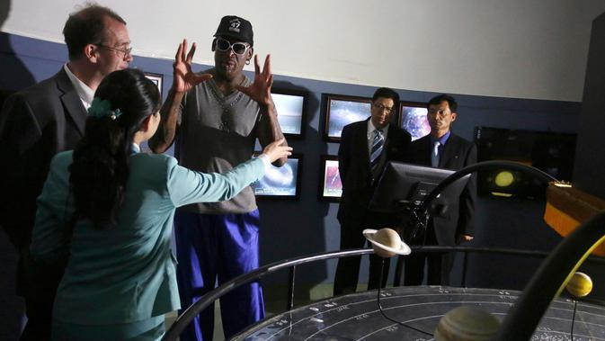 Dennis Rodman berbicara kepada seorang pemandu di Kompleks Sci-Tech di Pyongyang, Korea Utara (14/6). Rodman yang dekat dengan pemimpin Korut Kim Jong Un mulai beraktivitas di Pyongyang. (AP Photo/Kim Kwang Hyon)