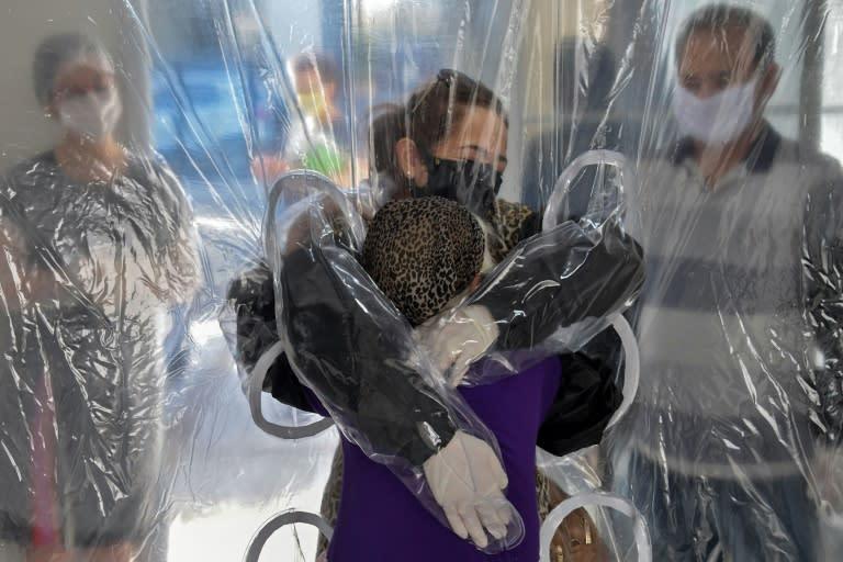 Elisabete Nagata (top) hugs her 76-year-old sister-in-law Luiza Nagata, through a transparent plastic curtain at a senior nursing home in Sao Paulo, Brazil, on June 13, 2020, amid the novel coronavirus (COVID-19) pandemic