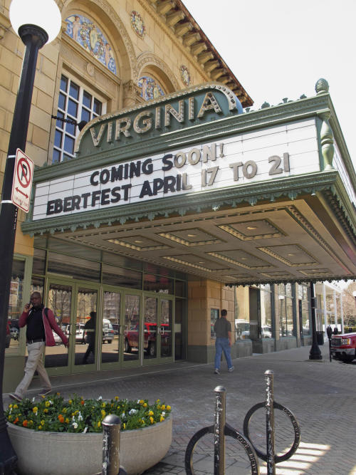 This April 5, 2013 photo shows people walking past the Virginia Theater in Champaign, Ill., with the marquee announcing the upcoming Ebertfest film festival running April 17-21. Through his television shows, movies reviews and essays, movie critic Roger Ebert belonged to the world beyond nearby Urbana, Ill. One part of Ebert's life that got little attention as the nation mourned his sudden death April 4 was how much he meant to this university town where he grew up. (AP Photo/David Mercer)