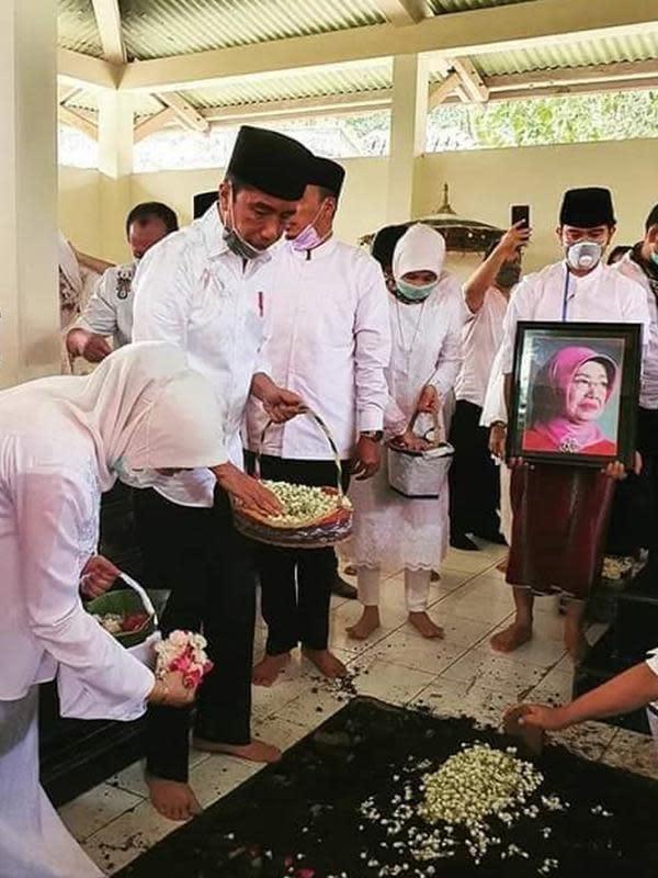 Presiden Joko Widodo atau Jokowi beserta keluarga menaburkan bunga di makam ibunda Sudjiatmi Notomihardjo di pemakaman keluarga di Mundu, Kabupaten Karanganyar, Jawa Tengah, Kamis (26/3/2020). Sujiatmi Notomiharjo wafat di RST Slamet Riyadi, Solo. (dok.istimewa)