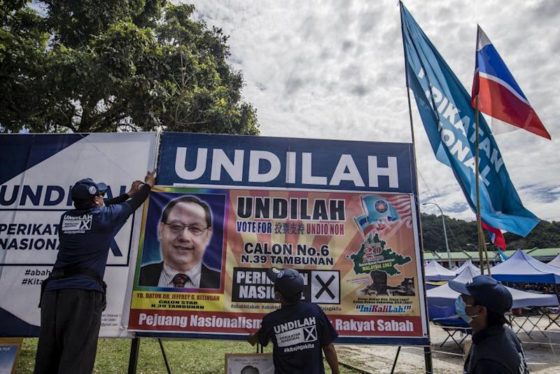 Workers are pictured putting up a poster of STAR president Datuk Jeffrey Kitingan in Tambunan September 24, 2020. — Picture by Firdaus Latif