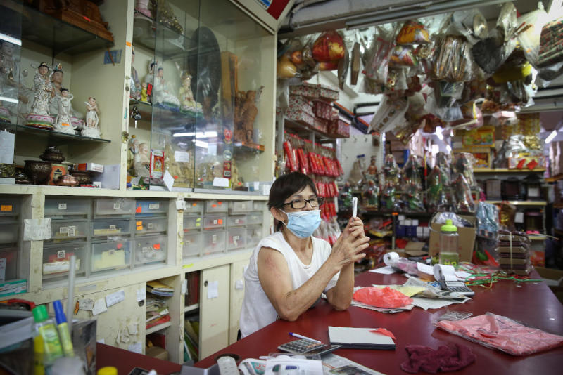 Sim Soom Hong, who owns a shop selling prayer items, has grown accustomed to her immigrant neighbours. ― Picture by Yusof Mat Isa