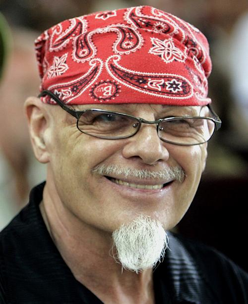 FILE - In this March 3, 2006 file photo, former British rocker Gary Glitter smiles at journalists prior to his verdict and sentencing at Ba Ria-Vung, Vung Tau province People's Court in Vietnam. Police investigating a sex abuse scandal surrounding late BBC television host Jimmy Savile have arrested pop star Gary Glitter in connection to the case, British media said Sunday, Oct. 28, 2012. Metropolitan Police said they arrested a man in his 60s early Sunday morning at his London home, on suspicion of sexual offenses. The force did not identify the man, but British media including the BBC and Press Association reported he was Glitter, 68, a former rock musician and a convicted sex offender. Glitter's real name is Paul Gadd. (AP Photo/Richard Vogel, File)
