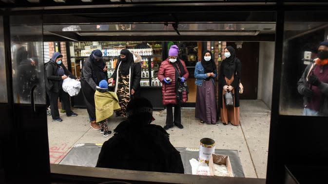 Orang-orang menunggu dalam antrean mengambil makan Halal gratis untuk Iftar selama bulan suci Ramadan di depan Masjid di masjid Taqwa di lingkungan Bedford-Stuyvesant di wilayah Brooklyn di New York (14/5/2020). (Stephanie Keith/Getty Images/AFP)