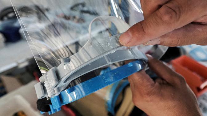 Pelindung wajah yang terbuat dari kombinasi plastik dan tekstil ditunjukkan di perusahaan Plaxtil, Chatellerault, Prancis, 25 Agustus 2020. Startup di Prancis, Plaxtil, mendaur ulang masker dan plastik untuk dijadikan pelindung wajah, pembuka pintu, dan pengencang masker. (GUILLAUME SOUVANT/AFP)