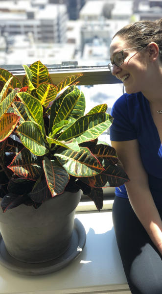 This May 2019 photo shows Molly Sprayregen gazing at one of her new house plants in Chicago, Ill., which she named Dylan. (Meredith Bennett-Swanson/Molly Sprayregen via AP)