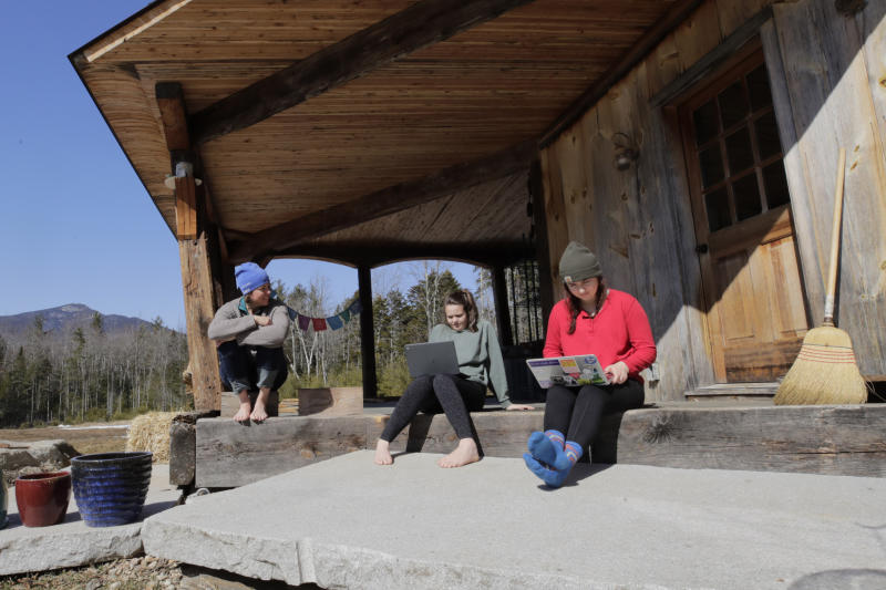 """Ashley Bullard, left, sits on the porch of her family's rural home in North Sandwich, N.H., as her daughters Raven, center, a senior in high school, and Willow, right, a freshman at Brandeis University, try to complete their classwork from home during the virus outbreak on a very limited internet connection, Thursday, March 26, 2020. In the town of 1,200 best known as the setting for the movie """"On Golden Pond,"""" broadband is scarce. Forget streaming Netflix, much less working or studying from home. Even the police department has trouble uploading its reports.    (AP Photo/Charles Krupa)"""