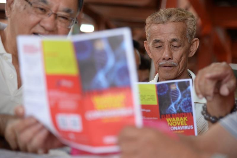 A man reading a pamphlet on novel coronavirus in Penang January 30, 2020. — Picture by Steven Ooi KE