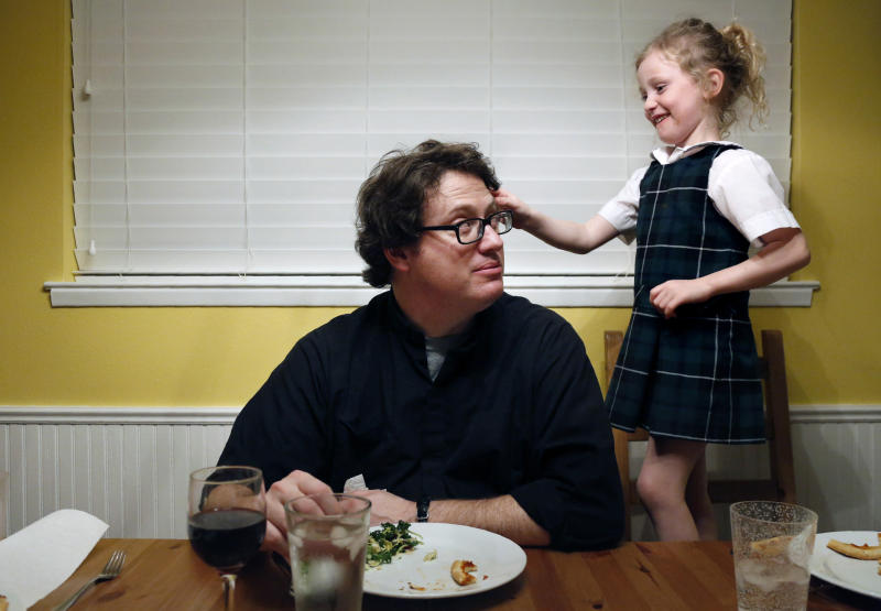 In this Feb. 7, 2020, photo, converted Catholic Priest Joshua Whitfield of north Dallas, left, looks up at his daughter Zoe-Catherine, 5, who stands on a kitchen chair pressing a pink butterfly clip into his hair during dinner in north Dallas. (AP Photo/Jessie Wardarski)
