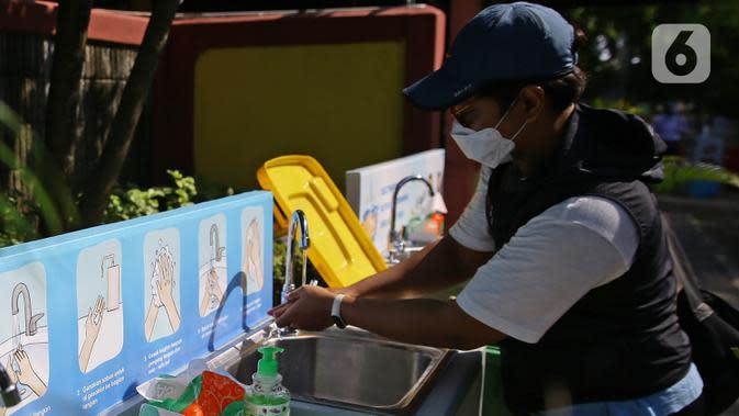 Pengunjung mencuci tangan memasuki Taman Margasatwa Ragunan, Jakarta, Sabtu (20/6/2020). Ragunan mulai dibuka kembali untuk pengunjung pada Sabtu ini di masa PSBB transisi dengan pembatasan dan penerapan protokol kesehatan yang ketat. (Liputan6.com/Herman Zakharia)