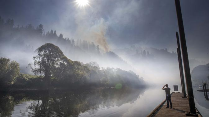 Asap terlihat di atas Sungai Siuslaw dekat Mapleton saat The Sweet Creek Milepost 2 Fire menyala di lereng bukit yang menghadap ke kota, Oregon, Amerika Serikat, 1 September 2020. (Chris Pietsch/The Register-Guard via AP)